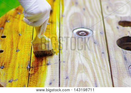 hand applying lacquer to a wood table with a brush .