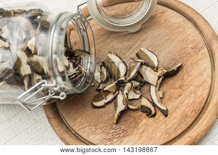 dried mushrooms in a glass bottle spilled on a wooden platter