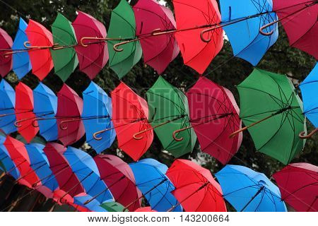 Many colorful umbrellas on the street weighs