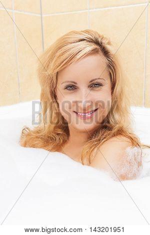 Spa Concepts. Caucasian Blond Woman Taking Foamy Bubble Bathtub and Enjoying. Vertical Image Orientation