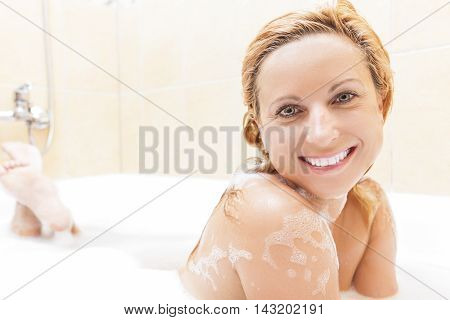 Smiling Caucasian Blond woman Taking Bathtub with Foam. Smiling Facial Expression.Horizontal Composition