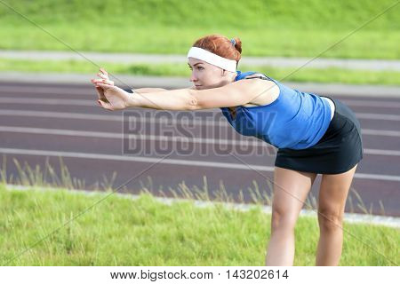 Young Red Haired Ginger Caucasian Female in Athletic Sportgear Making Arms Stretching Excercises Outdoors. Horizontal Image