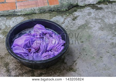 Soak dirty clothes in the basin black for cleansing,Thailand style family work ancient with detergent