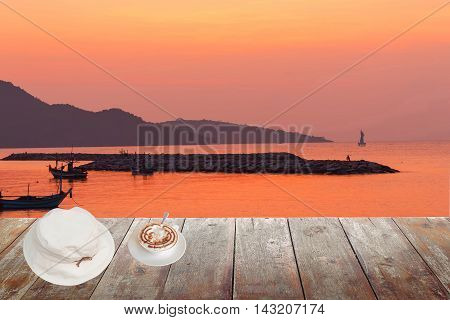 Morning coffee and White hat on wood table at sunset or sunrise sea The delicious aroma Cappuccino coffee : space for text and may be used as background :