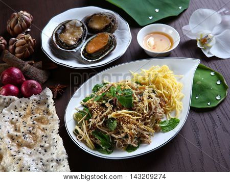 Abalone with special sliced pork and herbs salad with rice cracker on white plate in Vietnam restaurant