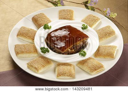 Grilled square biscuits with braised pork on white plate in restaurant