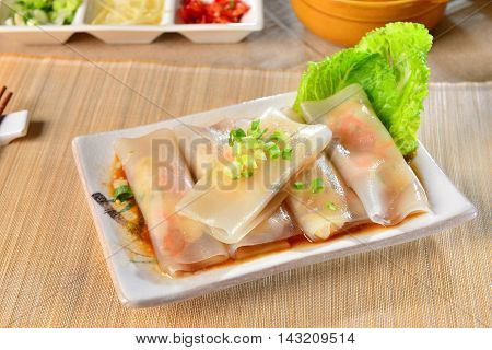 Fresh rolls of Pho with soyal sauce and green lettuce on white plate in Vietnam