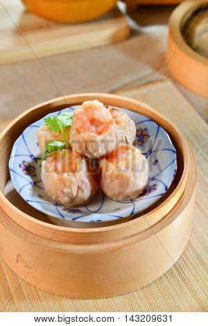 Shrimp Bao dumplings dishes sinks on bamboo tray in asian restaurant