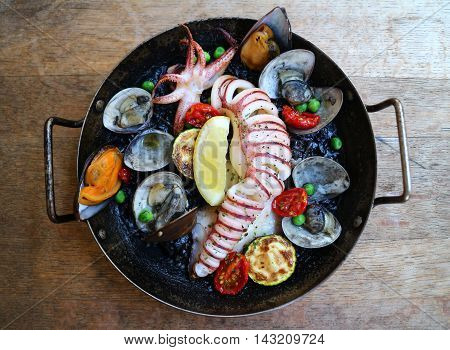 Spainish international cuisine orthodox with fried squid clams octopus lemon and mussel in black pan