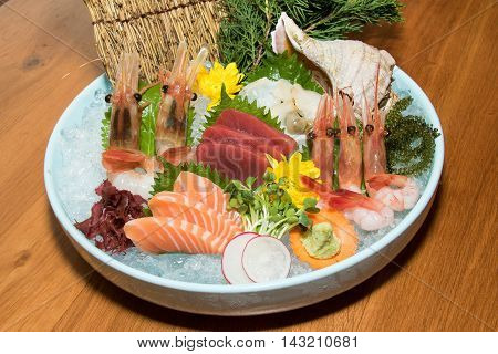 Bowl of sushi with shrimp tuna salmon shell oyster and sea grape on wooden table
