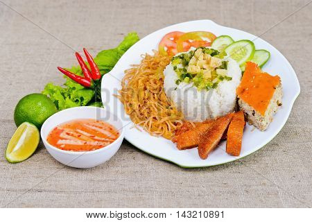 Special broken rice with fish sauce lemon fried pig skin sliced cucumber and chili on white plate in Vietnam