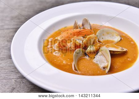 Fresh wild mushroom soup with clams and shrimps on white plate