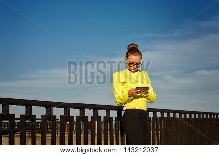 Girl checks email outdoors. Business woman at work. Correspondence. Wireless technologies.
