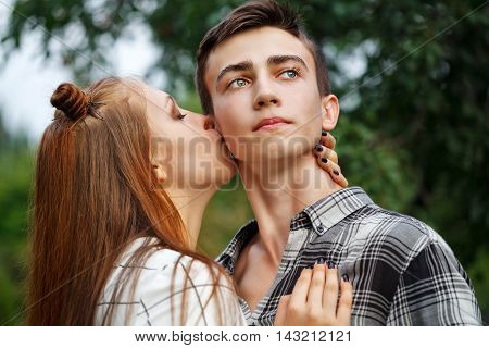 Loving couple teenagers. Girlfriend and boyfriend together. The girl kisses a guy on the cheek. Close-up. First love. He falls in love. Date.
