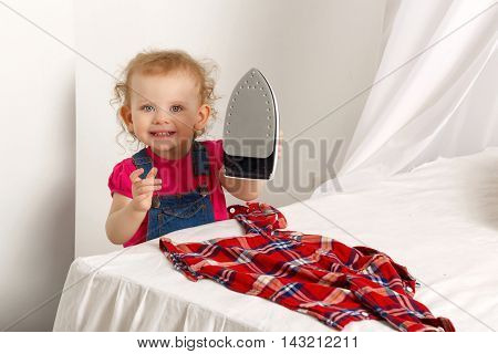 A cute little girl with iron to iron plaid shirt. Mom's helper. Household chores.