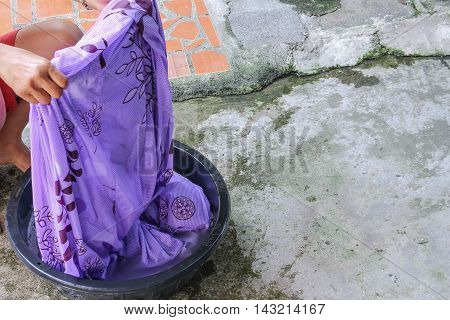 Woman washing dirty clothes in the basin black  for housework cleansing and soak with detergent in the evening Thailand  style ancient