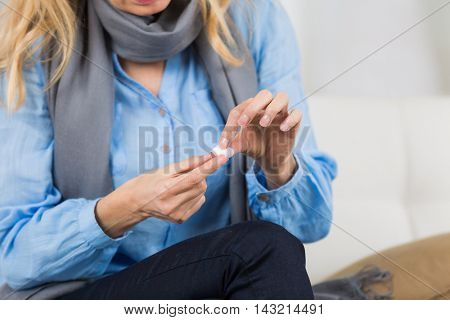 beautiful woman is putting adhesive tape on her finger