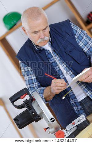 senior carpenter marking a measurement