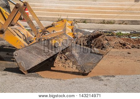 Excavator working on the Repair of pipe water and sewerage on road Worker using a small excavator to dig a hole to fix a water.