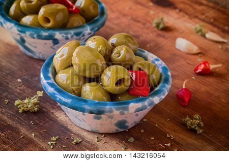 Preserves. Green Marinated Olives in ceramic Bowls with Chili, Oregano. Close-up