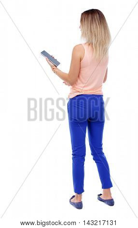 back view of standing young beautiful  woman using a mobile phone or tablet computer. girl  watching. Rear view people collection.  backside view of person.  Isolated over white background. The blonde