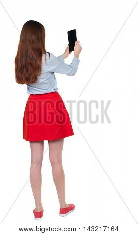 back view of standing young beautiful  woman  using a mobile phone. girl  watching. Rear view people collection.  backside view of person.  Isolated over white background. Long-haired brunette in red