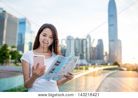 Woman looking at paper map and using mobile phone