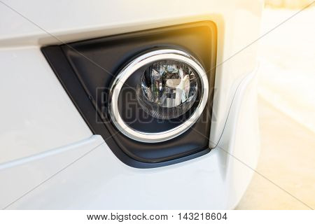 Closeup headlights of modern white car with light