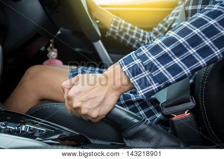 Closeup of young woman pulling handbrake lever in car
