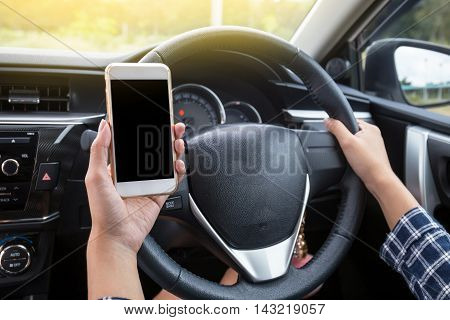 Young female driver using touch screen smartphone and hand holding steering wheel in a car.