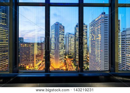 modern office buildings in downtown of tokyo at twilight on view from glass window