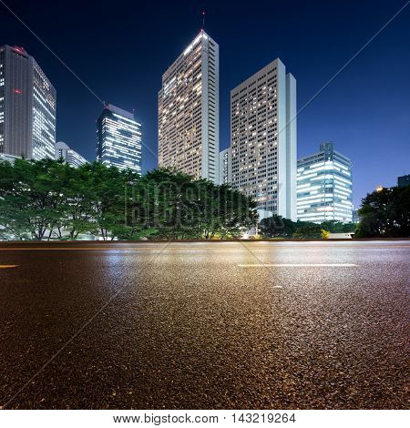 modern office buildings in tokyo at twilight from empty asphalt road