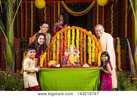 cheerful indian  family welcoming lord Ganesha idol on ganesh festival or ganesh chaturthi on palkhi decorated with garland flowers