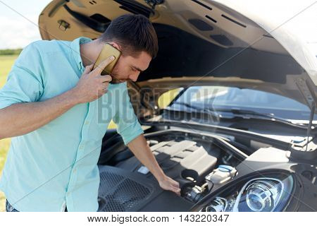 road trip, transport, travel, technology and people concept - young man with smartphone and open hood of broken car at countryside calling to evacuation service