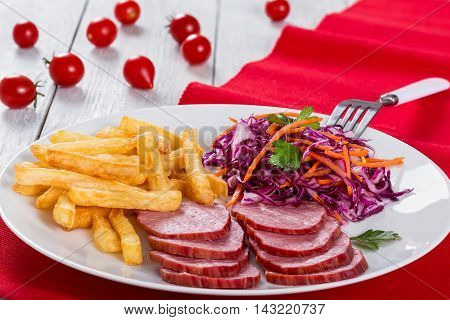 sliced smoked veal fillet french fries and red cabbage salad with carrots cut into strips and parsley dressing with vinegar and olive oil on table mat with cherry tomatoes on white rustic boards close-up