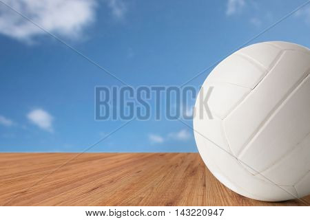 sport, fitness, game, sports equipment and objects concept - close up of volleyball ball over blue sky and wooden floor background