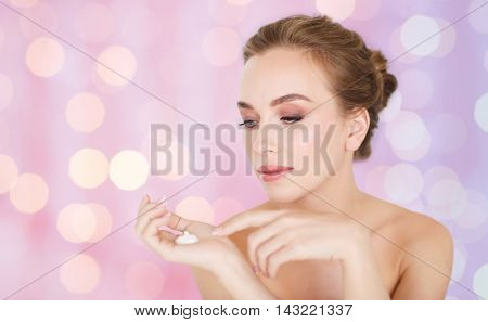 beauty, people, skincare and cosmetics concept - happy young woman with moisturizing cream on hand over rose quartz and serenity lights background