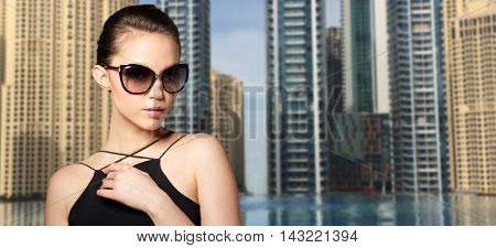 accessories, eyewear, fashion, people and luxury concept - beautiful young woman in elegant black sunglasses over dubai city street background
