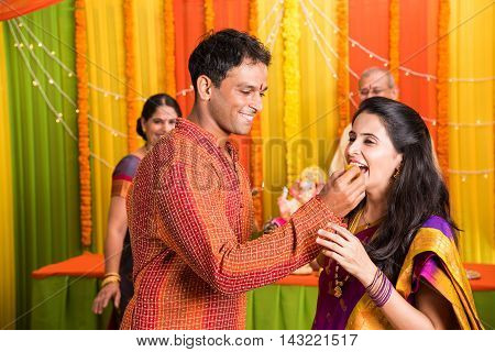 indian husband making his wife eat sweet bundi laddu on the occassion of ganesh festival,  idol of lord ganesh and parents in the background