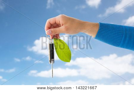conservation, environment, people, transport and ecology concept - close up of hand holding car key with green leaf trinket over blue sky and clouds background