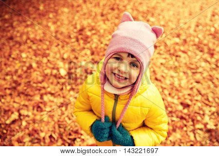 autumn, childhood, nature and people concept - happy little girl over fallen leaves in park