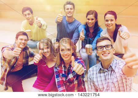 education, high school, friendship, drinks and people concept - group of smiling students with paper coffee cups showing thumbs up gesture