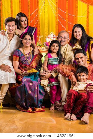 group photo of happy indian family in ganesh festival, happy indian family celebrating ganpati festival or ganesh utsav or ganesh festival