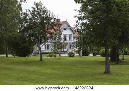 RURAL COUNTY, SWEDEN ON JULY 22. View of a building beyond a garden park on July 22, 2016 in Grundsunda, Sweden. Trees and green lawn this side. Overcast, summer. Editorial use.