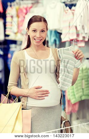 pregnancy, people, sale and expectation concept - happy pregnant woman with shopping bag buying baby bodysuit at children clothing store
