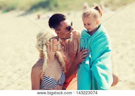 family, vacation, adoption and people concept - happy man, woman and little girl in blanket or towel on summer beach