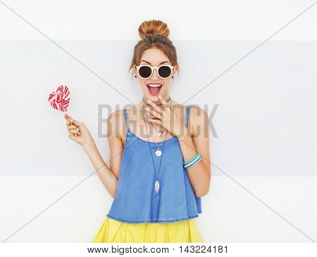 Beautiful girl with candy on color background
