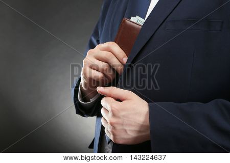 Businessman putting wallet with banknotes in suit pocket. Corruption concept