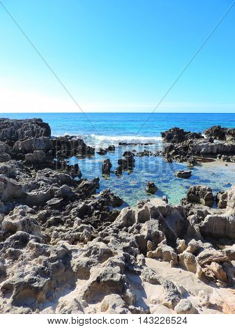 Rough coastline and turquoise sea, coastal feature with low tide.