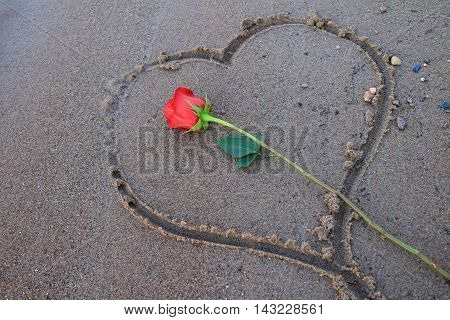 Red rose laying in a drawn heart in the sand.